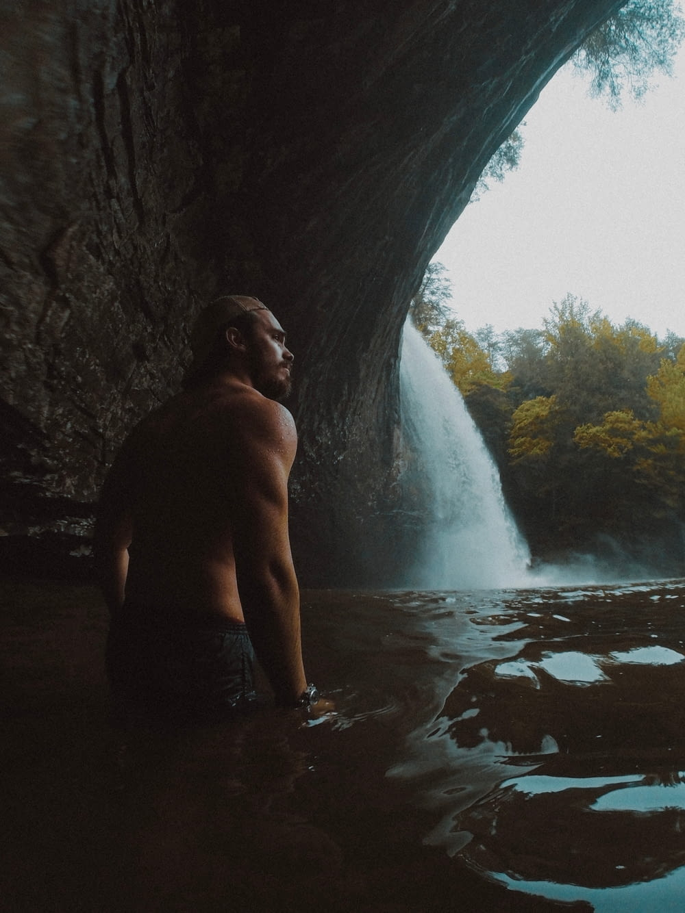topless man in black shorts standing in cave