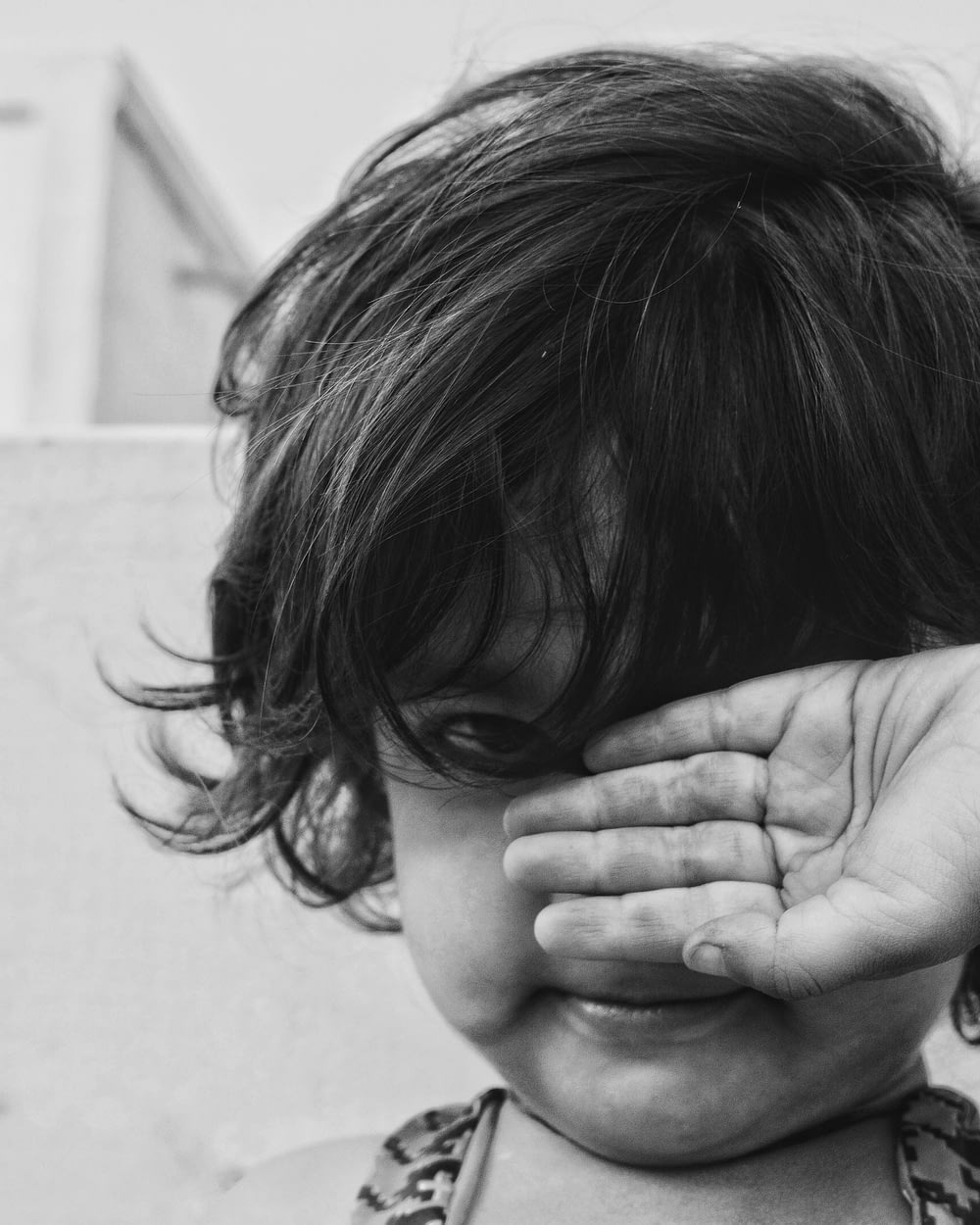 grayscale photo of child holding his face