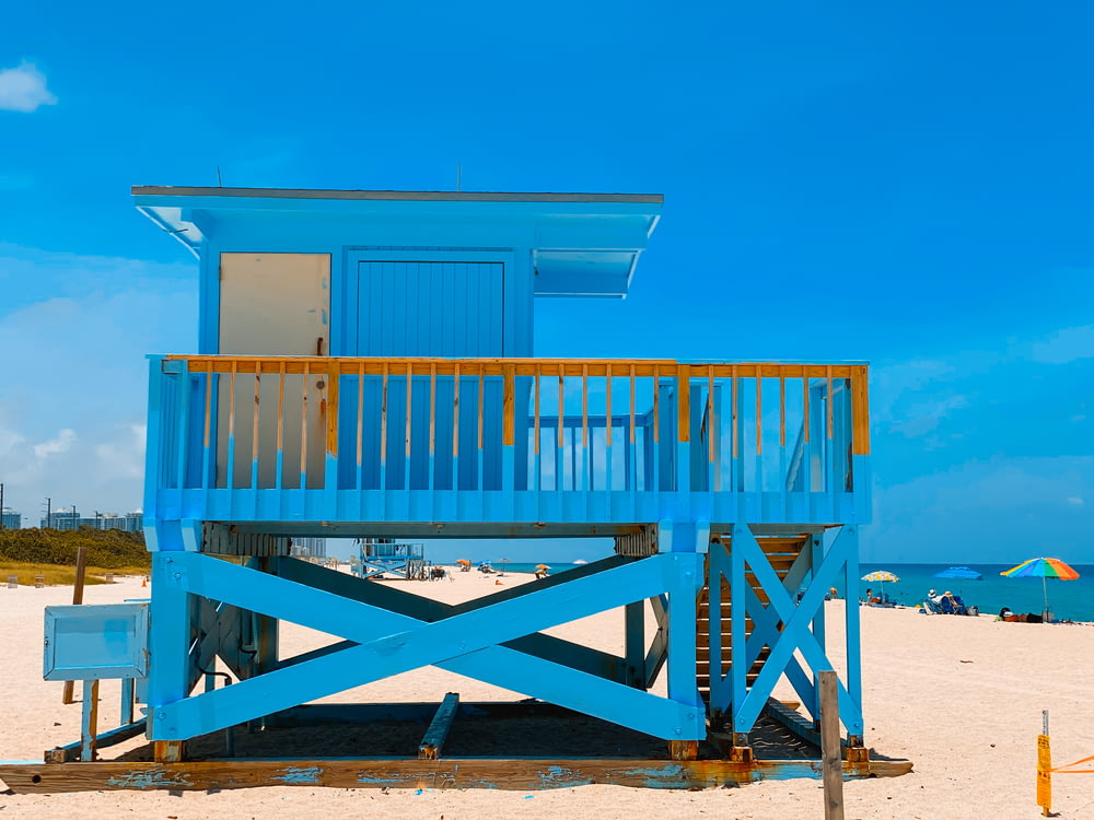 blue wooden dock on beach during daytime