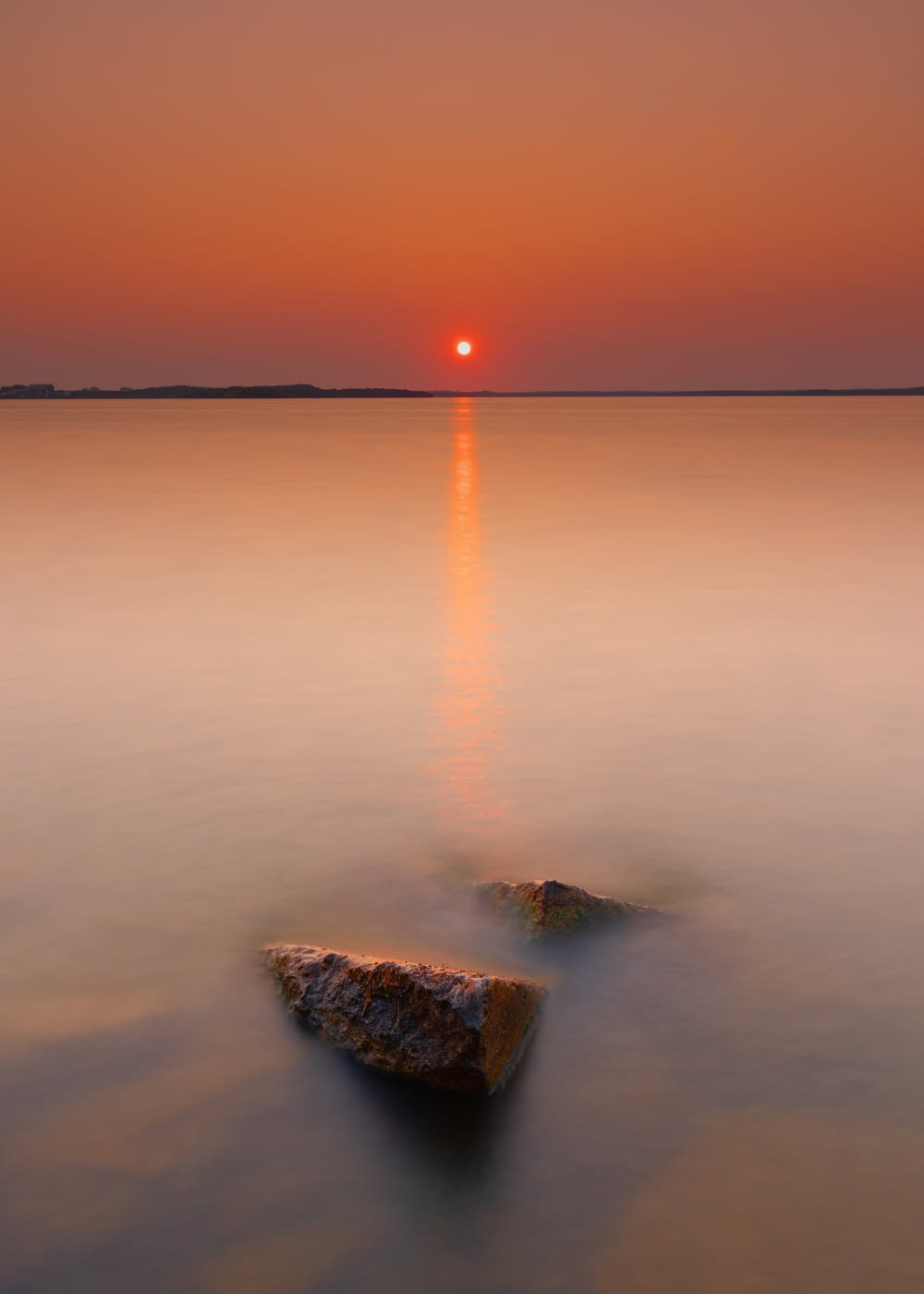 brown rock formation on body of water during sunset