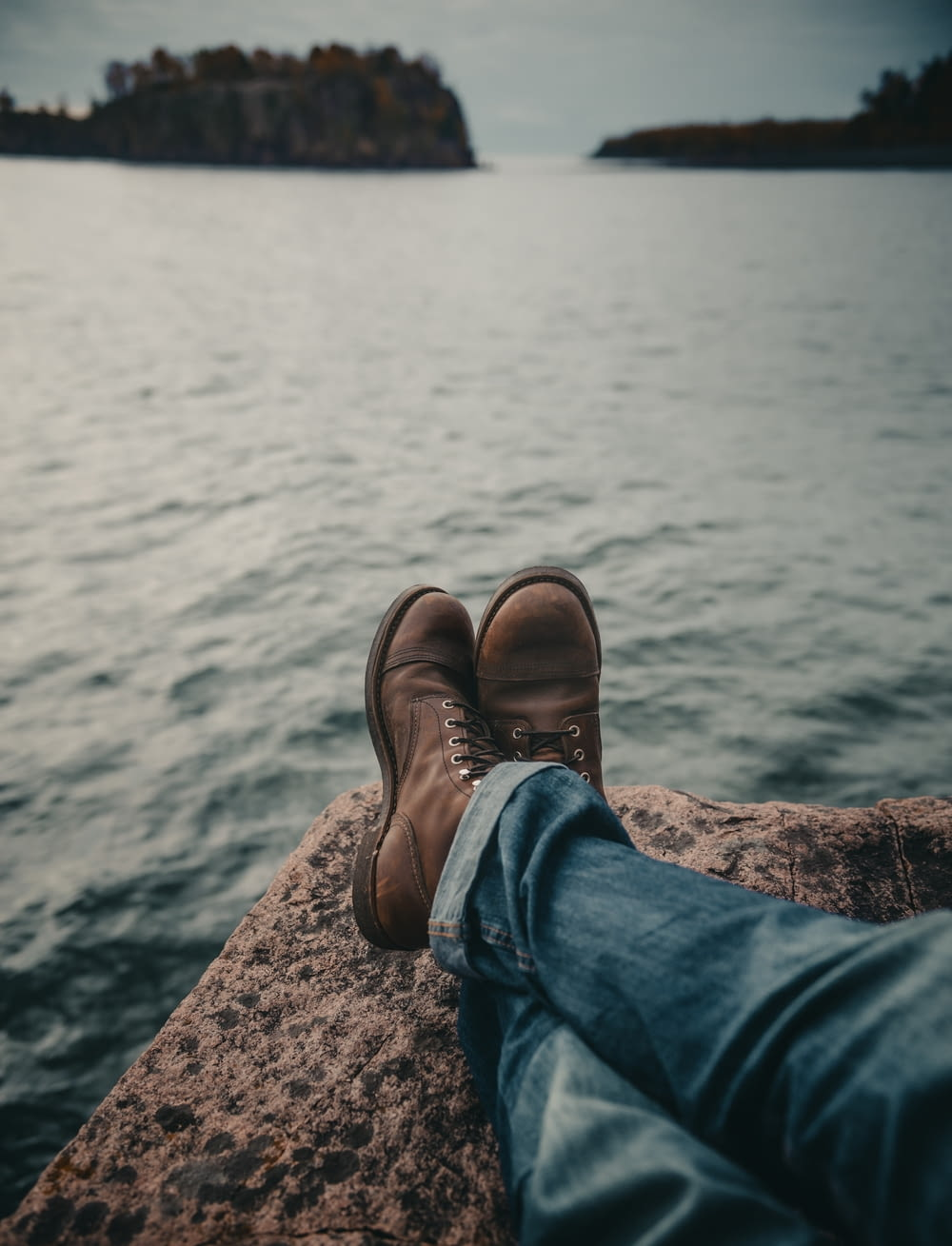 person in blue denim jeans and brown leather boots sitting on rock near body of water