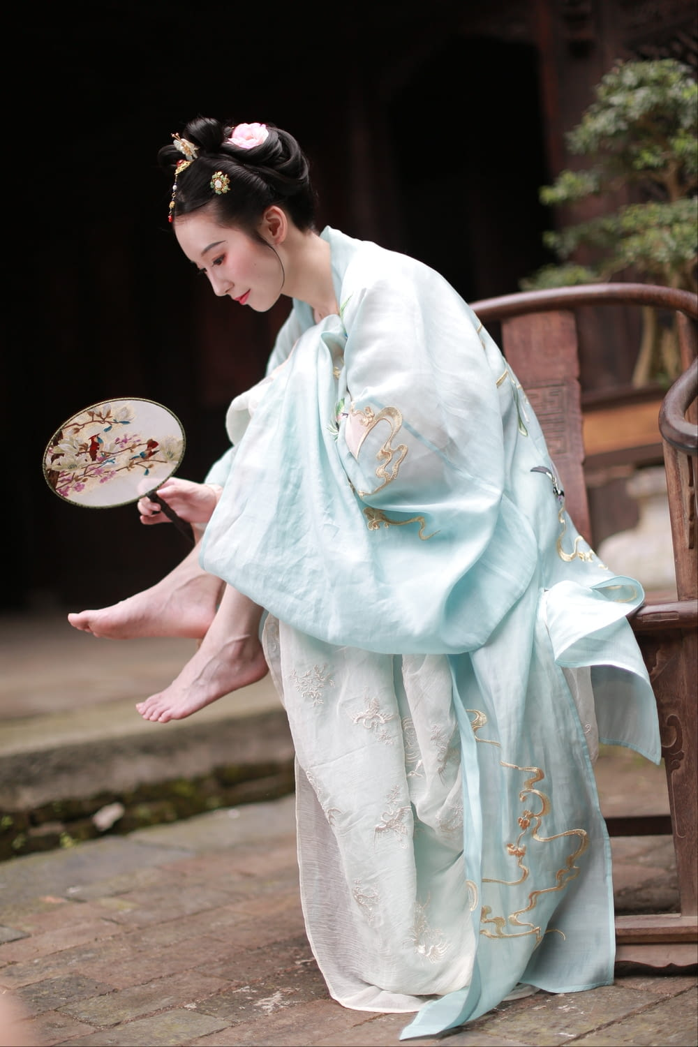 woman in white and blue floral kimono holding white and pink floral hand fan