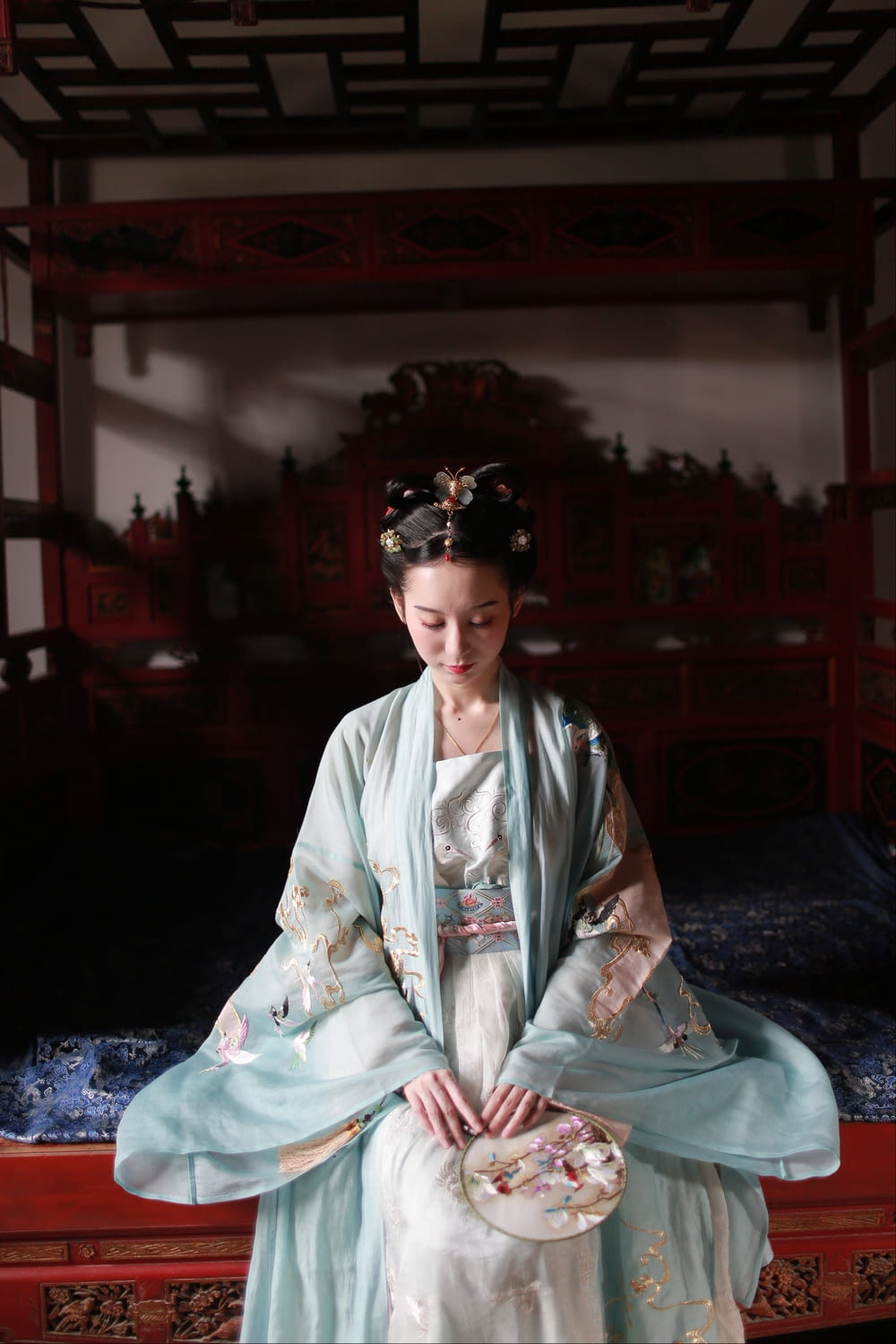 woman in white robe sitting on bed