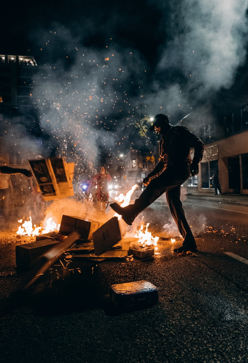man in black t-shirt and black pants holding fire