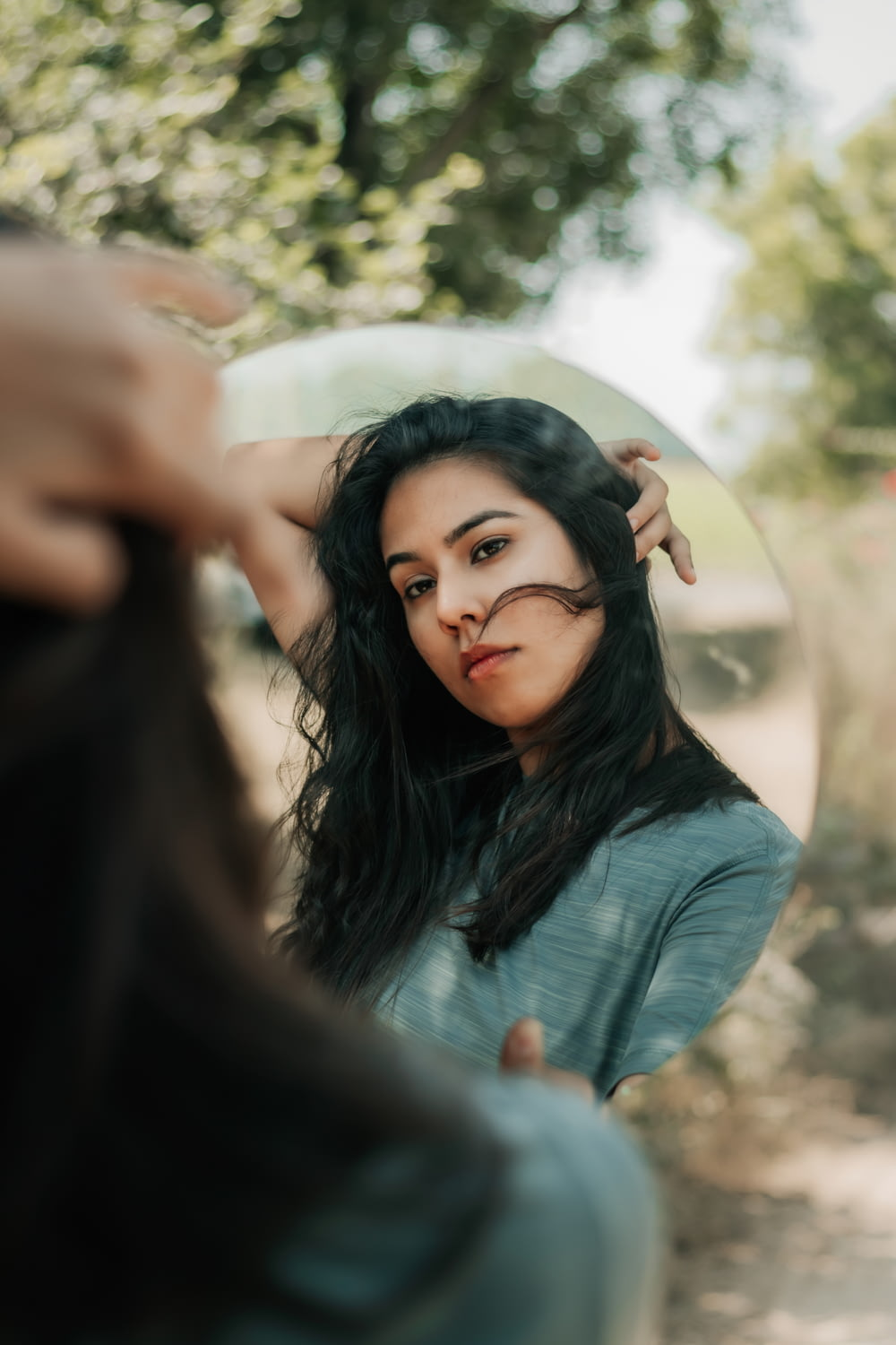 woman in black long sleeve shirt holding her hair