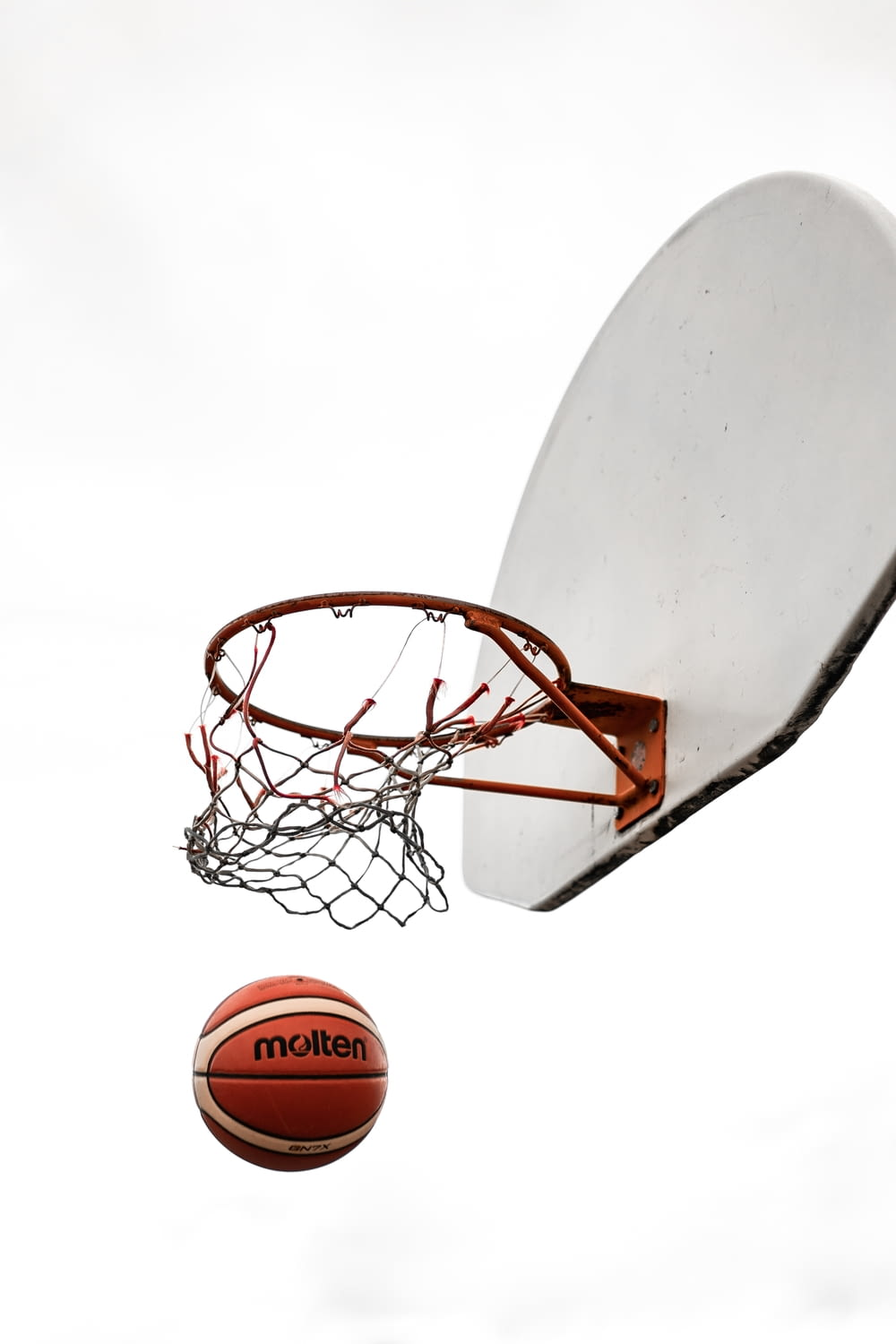 basketball on basketball hoop with white background