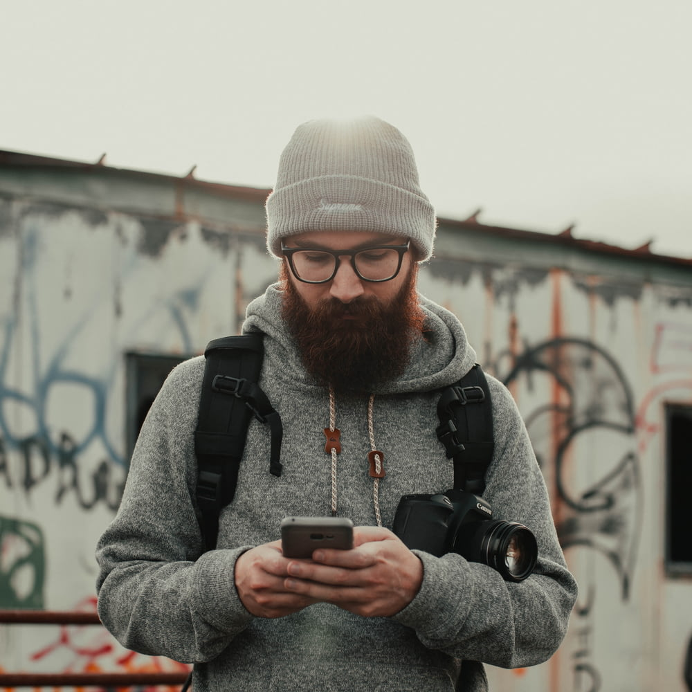 man in gray knit cap and black jacket holding black smartphone
