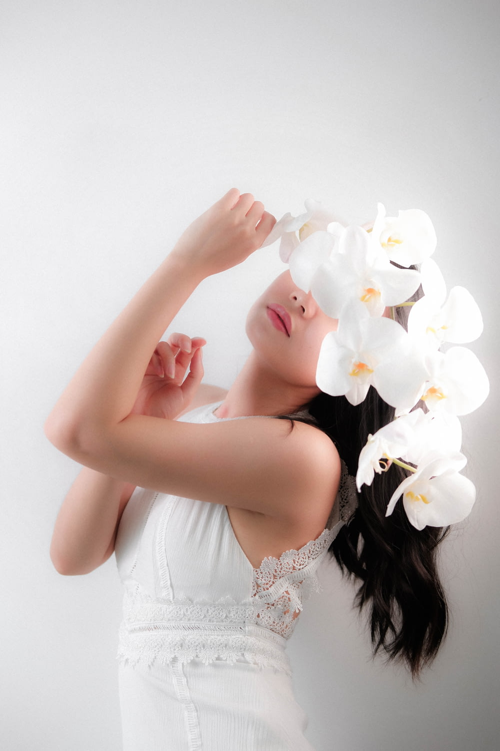 woman in white floral dress holding white flower