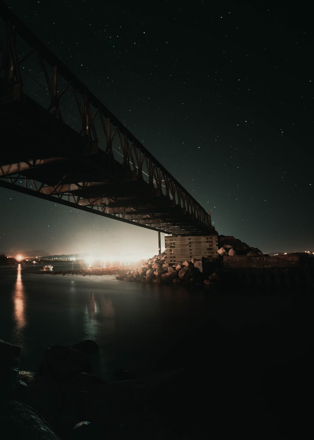 brown bridge over body of water during night time