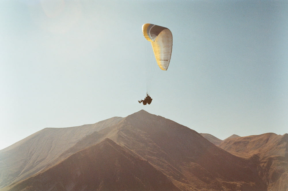 person in parachute over the mountain during daytime