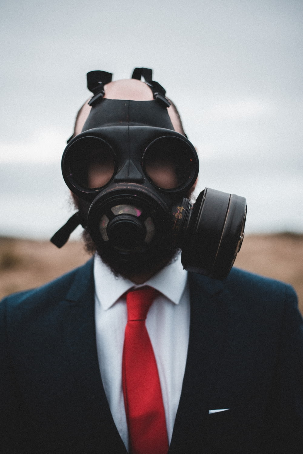 man in blue suit wearing black gas mask