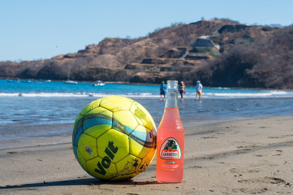 yellow and red soccer ball on beach during daytime