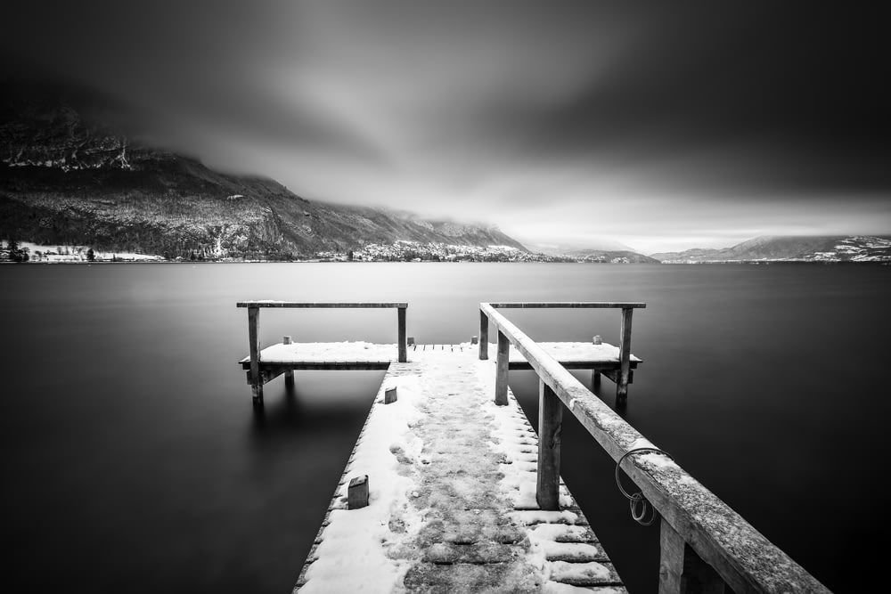 grayscale photo of wooden dock on lake