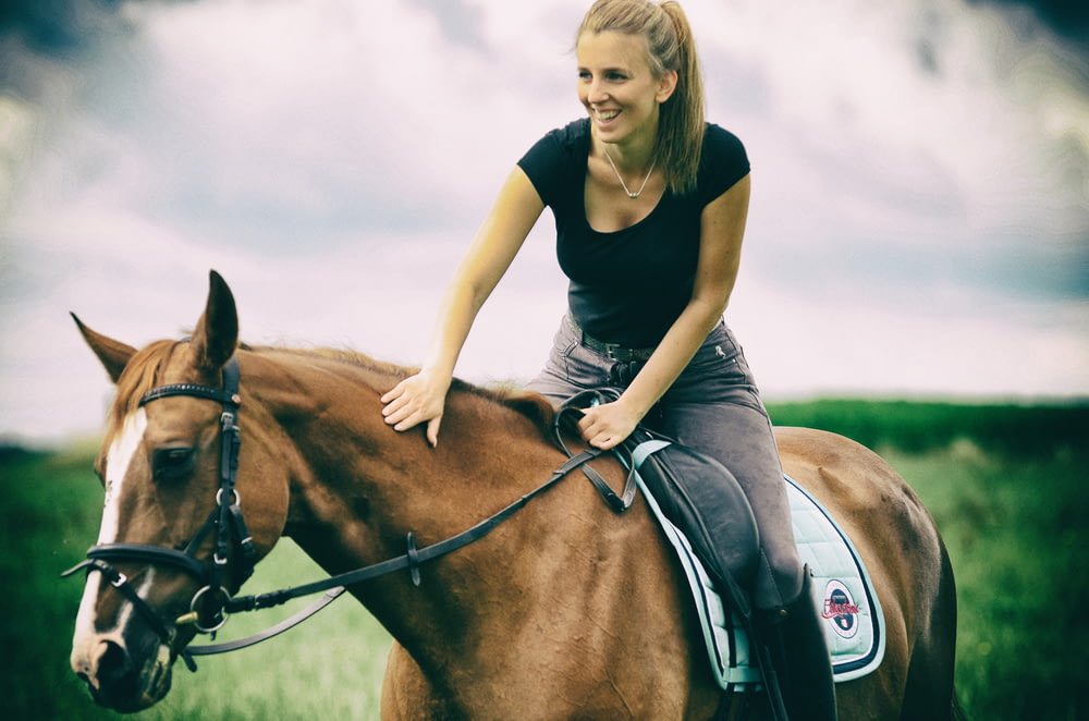 woman in blue crew neck t-shirt riding brown horse during daytime