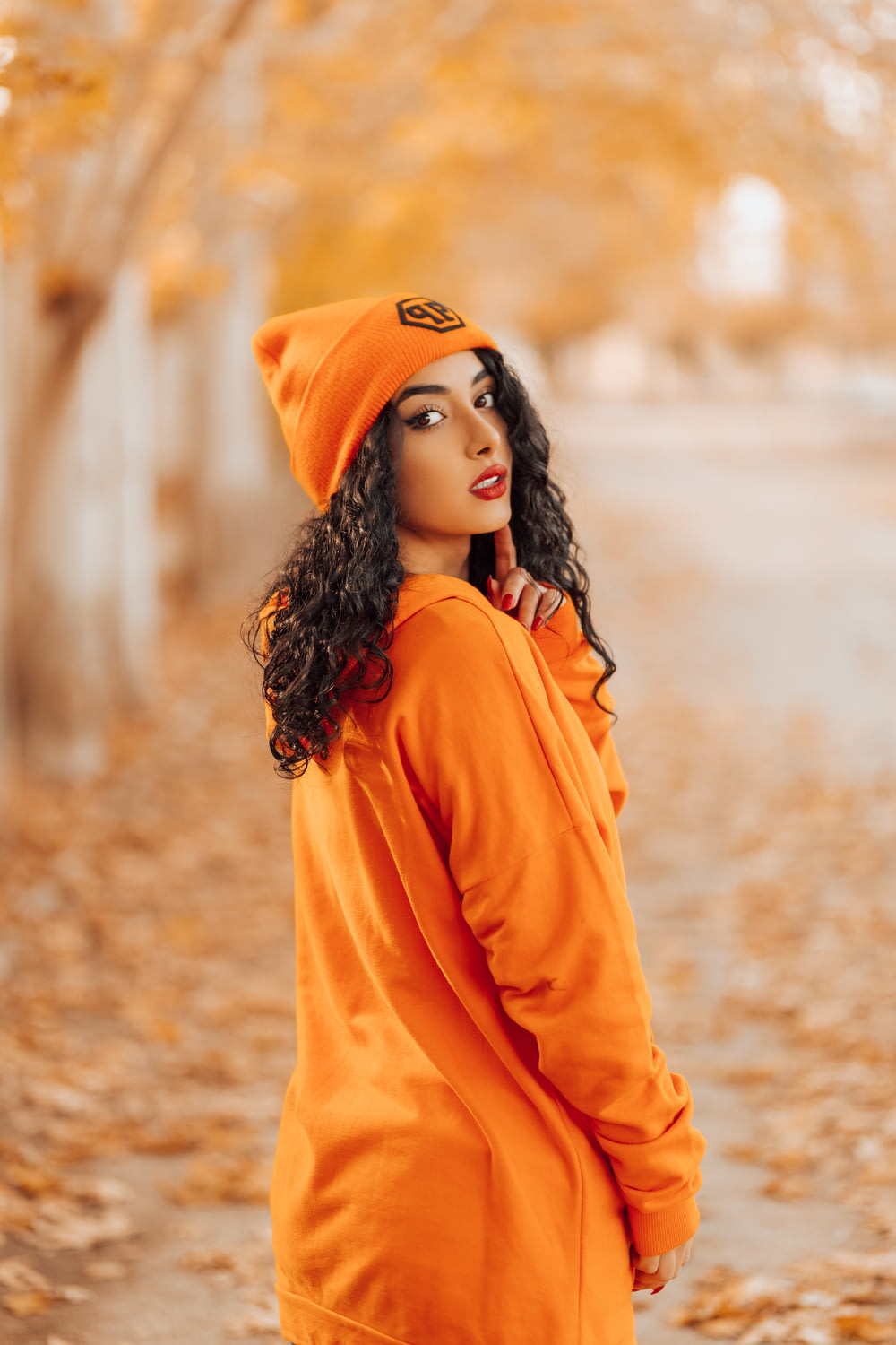 woman in orange hoodie standing on brown soil during daytime