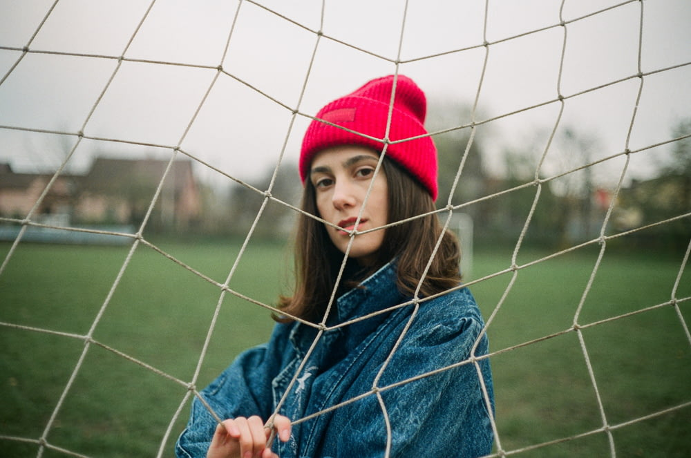 woman in blue denim jacket and red knit cap standing near gray metal fence during daytime