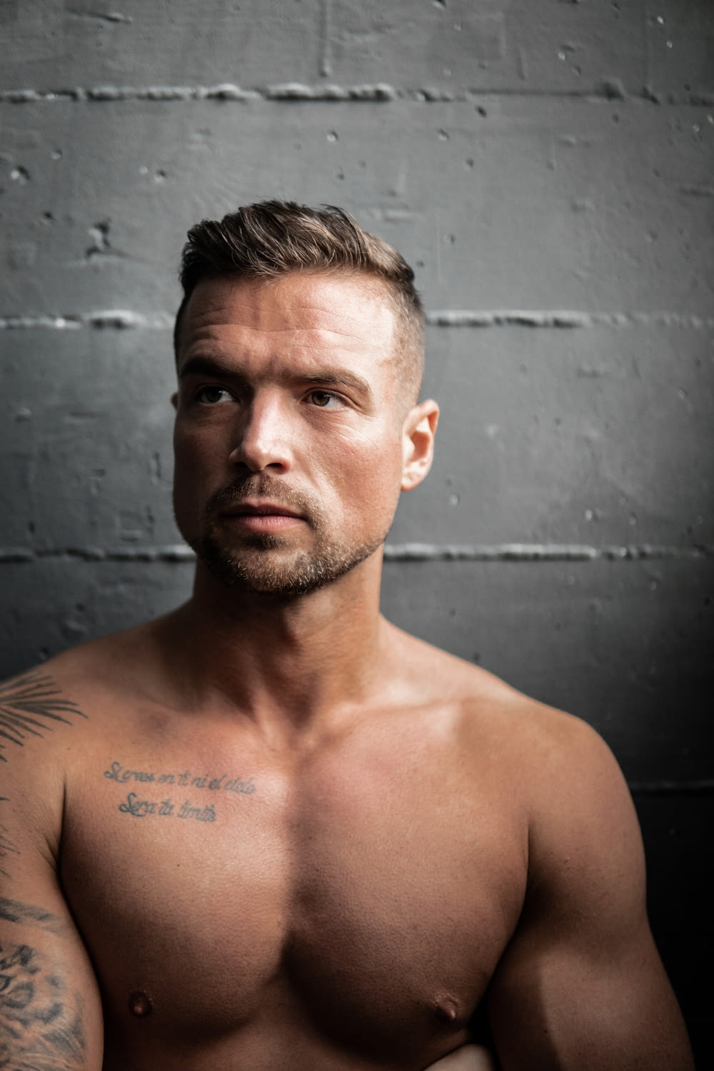 topless man leaning on gray wall