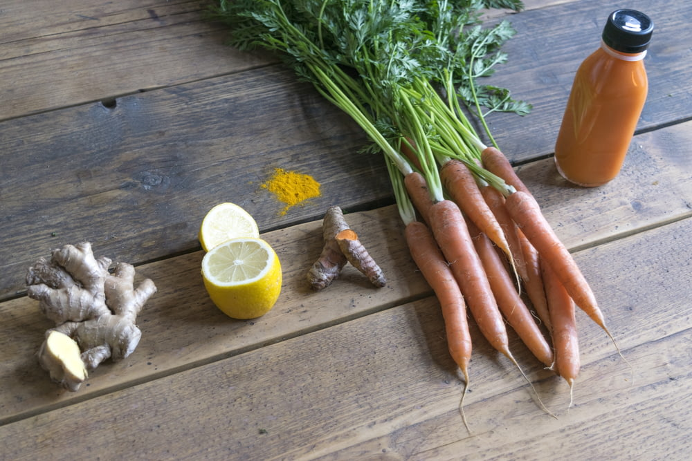 carrot and green vegetable on brown wooden table