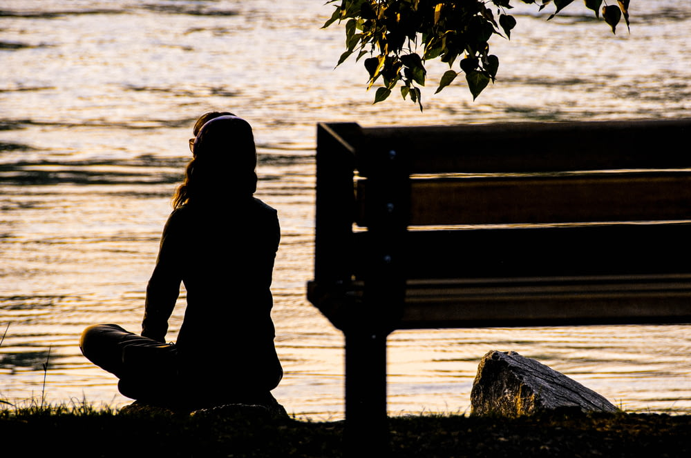silhouette of person sitting on bench near body of water during daytime