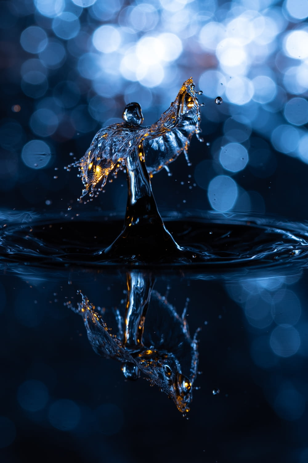 water drop on water in close up photography