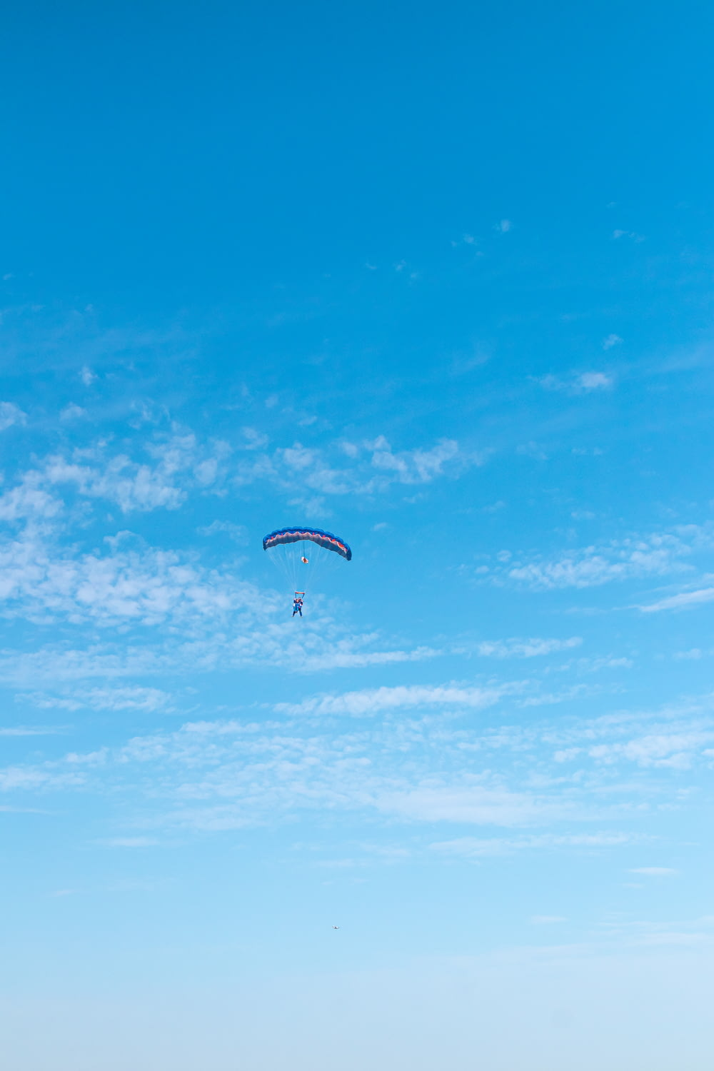 person in parachute under blue sky during daytime