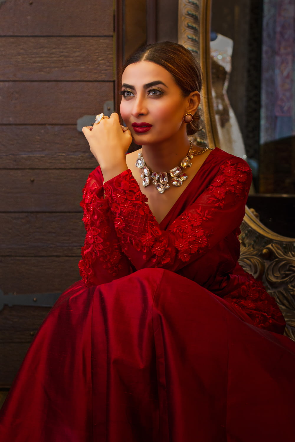 woman in red dress sitting on brown wooden bench
