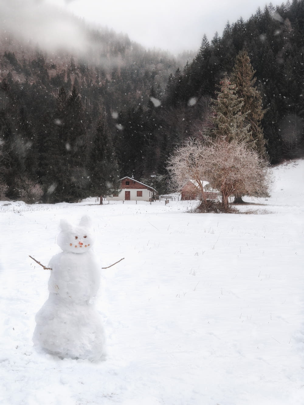 white snowman on snow covered ground during daytime