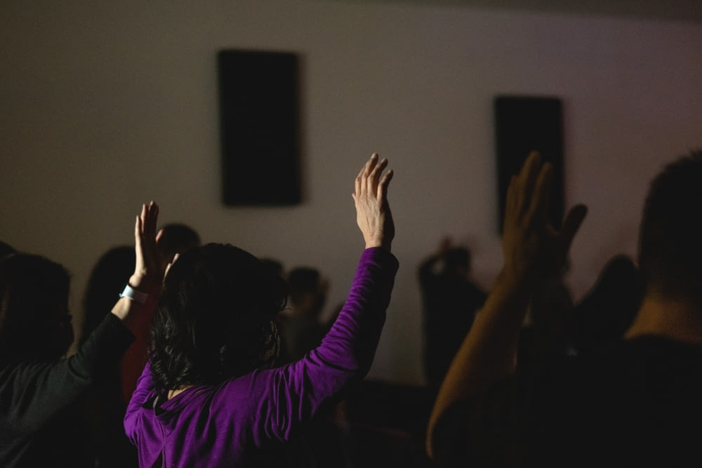 woman in purple long sleeve shirt raising her hands