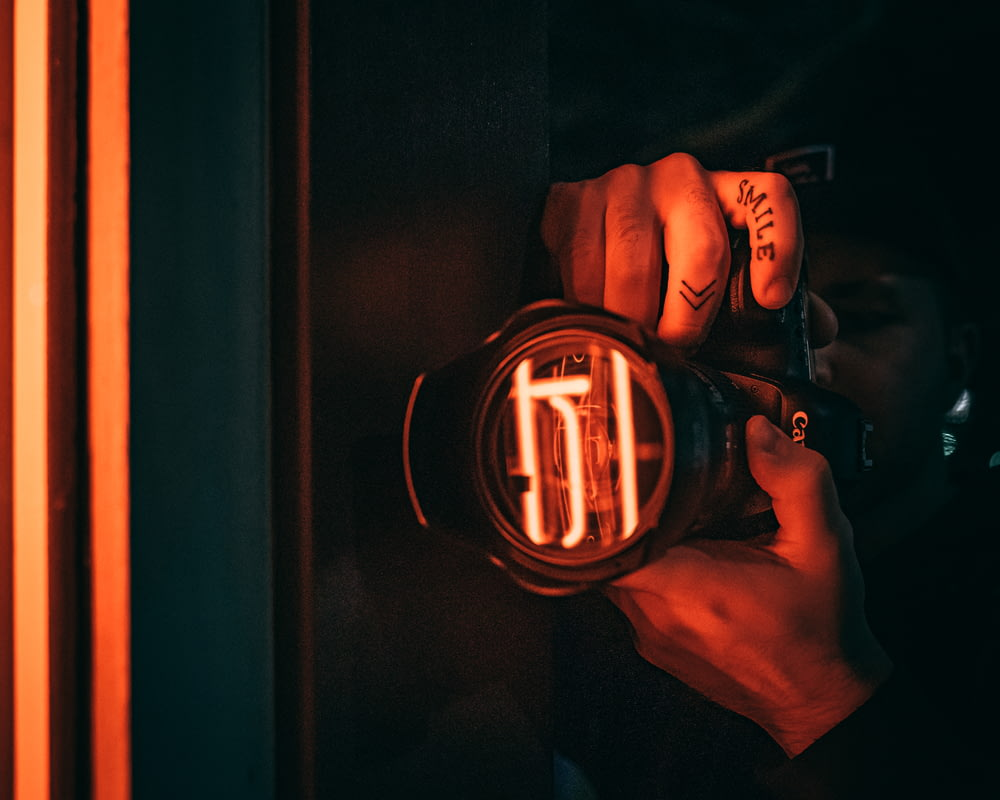 person holding black and orange led watch