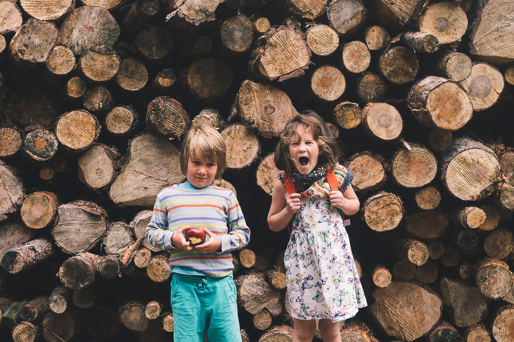 girl in white and pink shirt standing beside brown wood logs