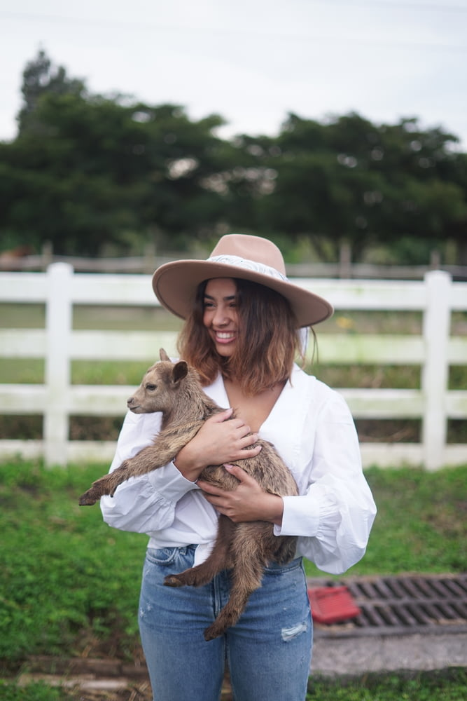 girl in white long sleeve shirt and brown cowboy hat holding brown animal during daytime
