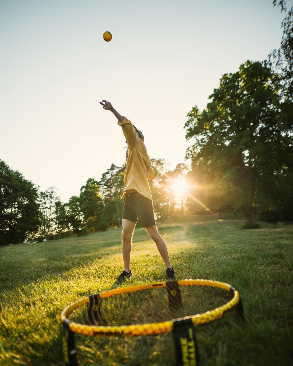 woman in white dress jumping on yellow round trampoline during daytime