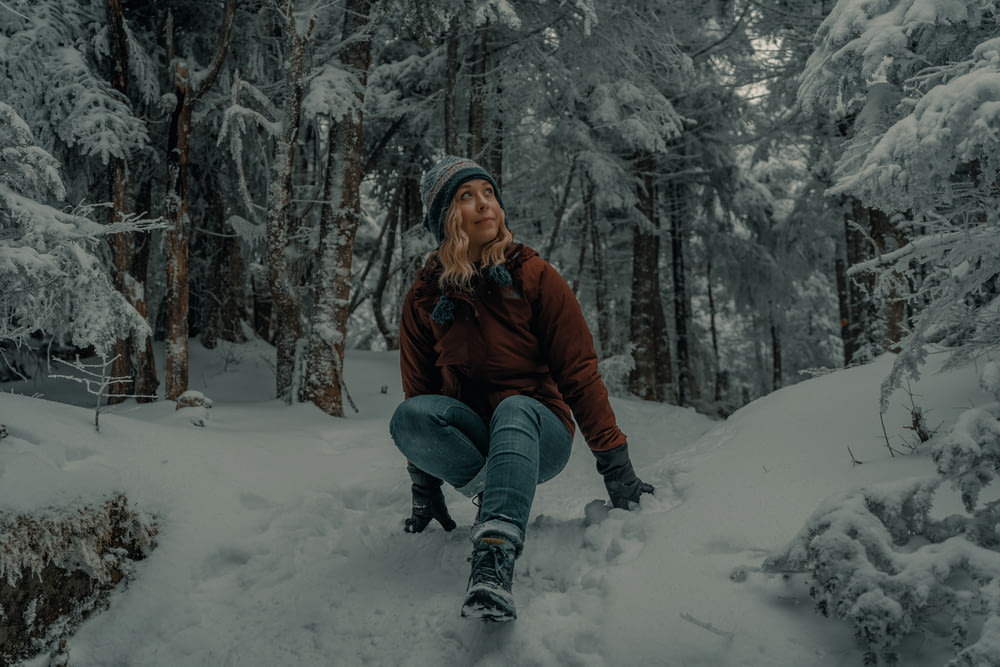 woman in brown jacket and blue denim jeans sitting on snow covered ground