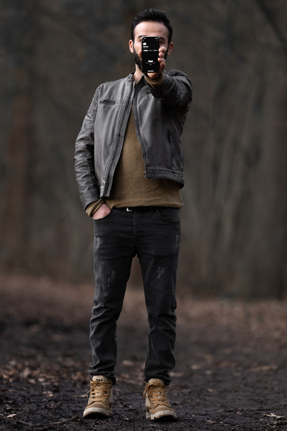 man in gray jacket and blue denim jeans standing on brown field during daytime