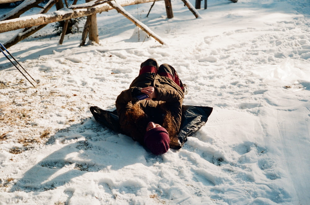 person lying on snow covered ground during daytime
