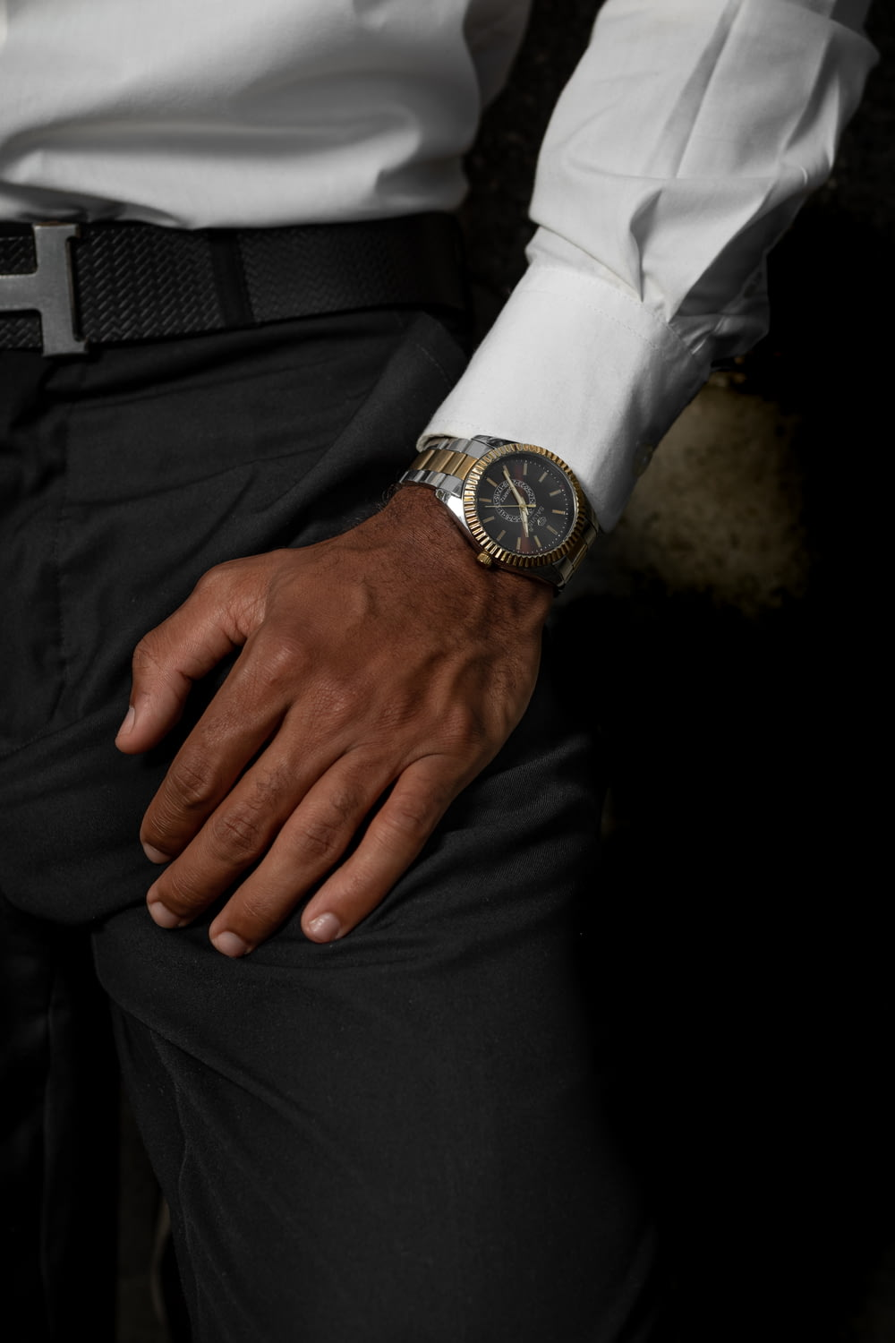 person in black pants wearing silver watch