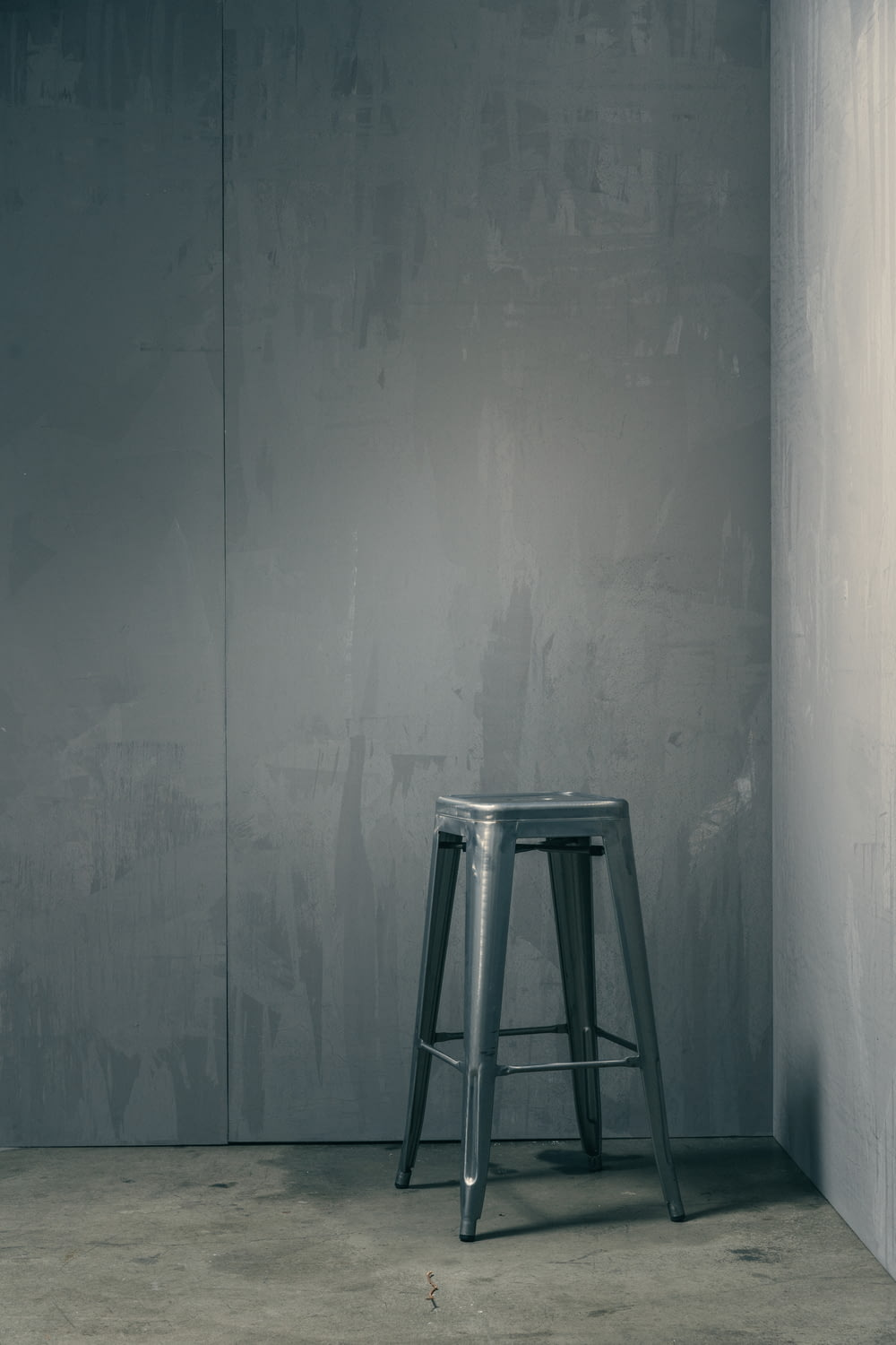gray wooden seat beside white wall