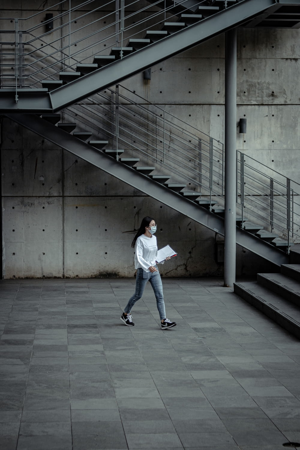 woman in white long sleeve shirt and blue denim jeans walking on gray concrete floor