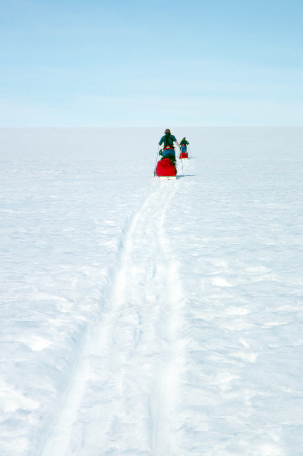 2 person in red and black jacket riding on snow board during daytime