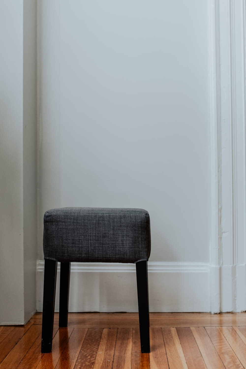 gray and black chair beside white wall