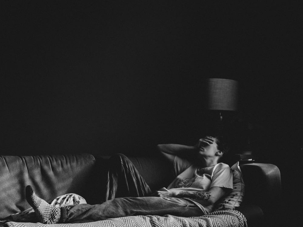 man in black t-shirt lying on couch