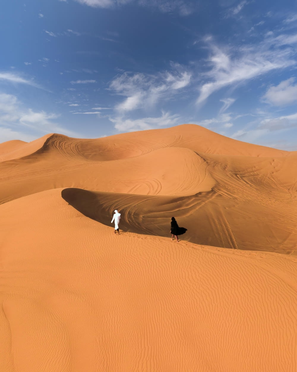 man in black jacket and white pants standing on brown sand under blue sky during daytime