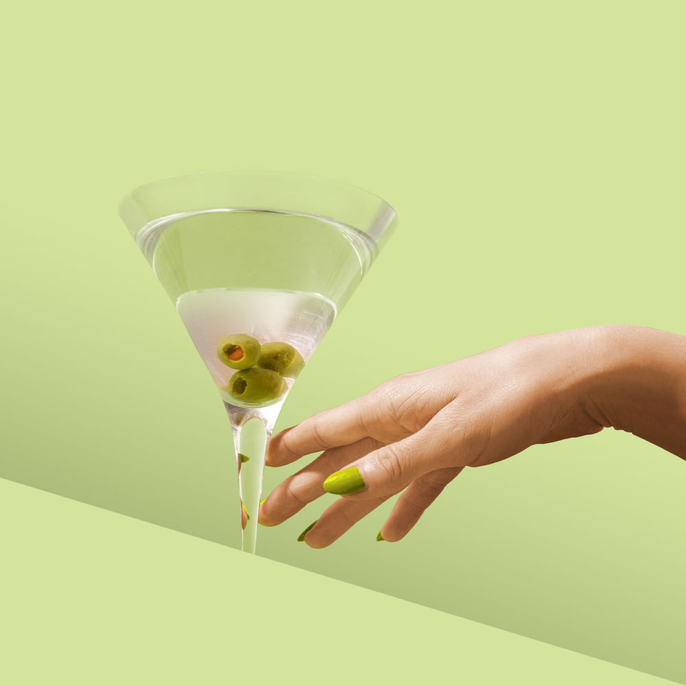 person holding clear drinking glass with white liquid