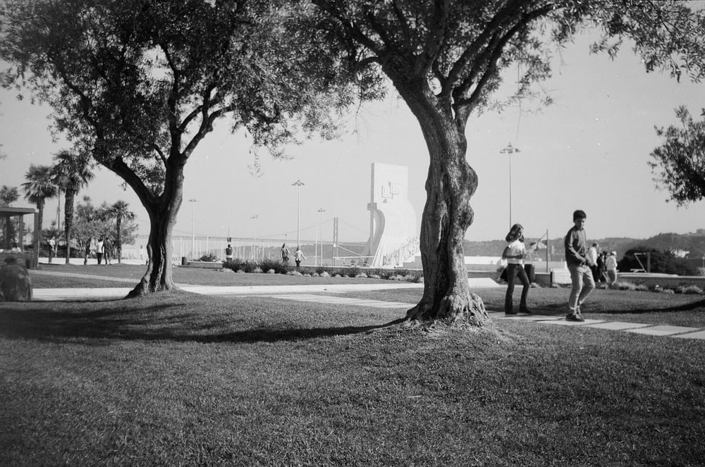 grayscale photo of people walking on park
