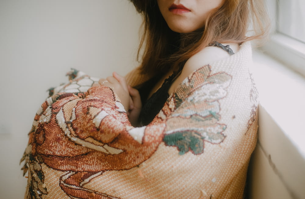 woman in white and brown floral sweater