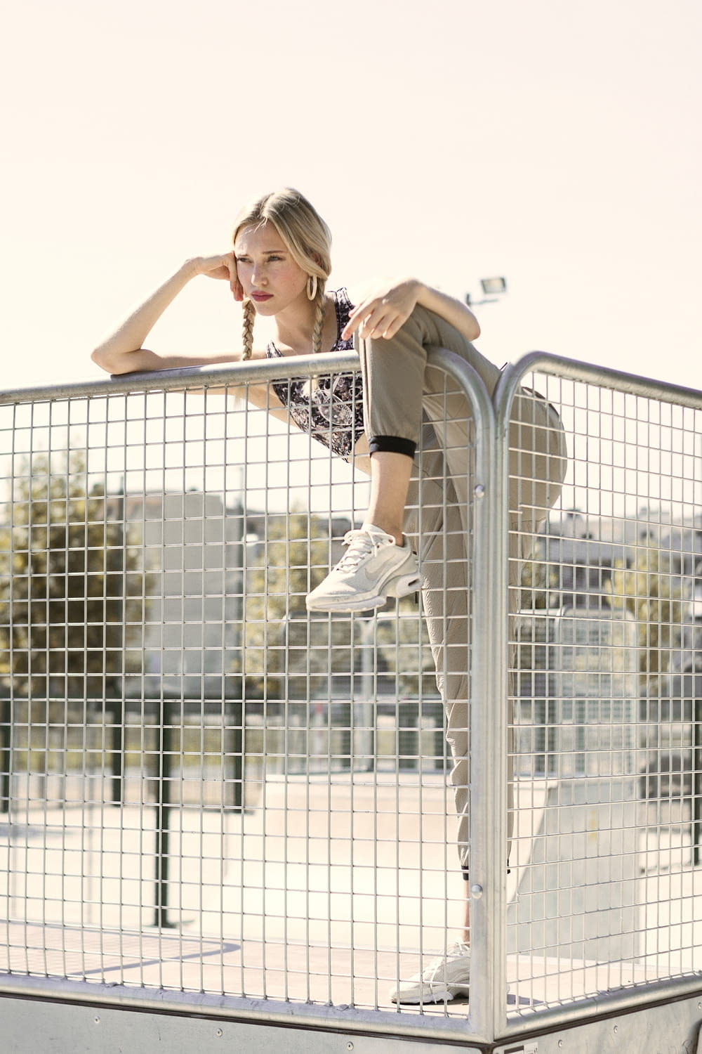 woman in black and white shirt and black pants leaning on gray metal fence during daytime