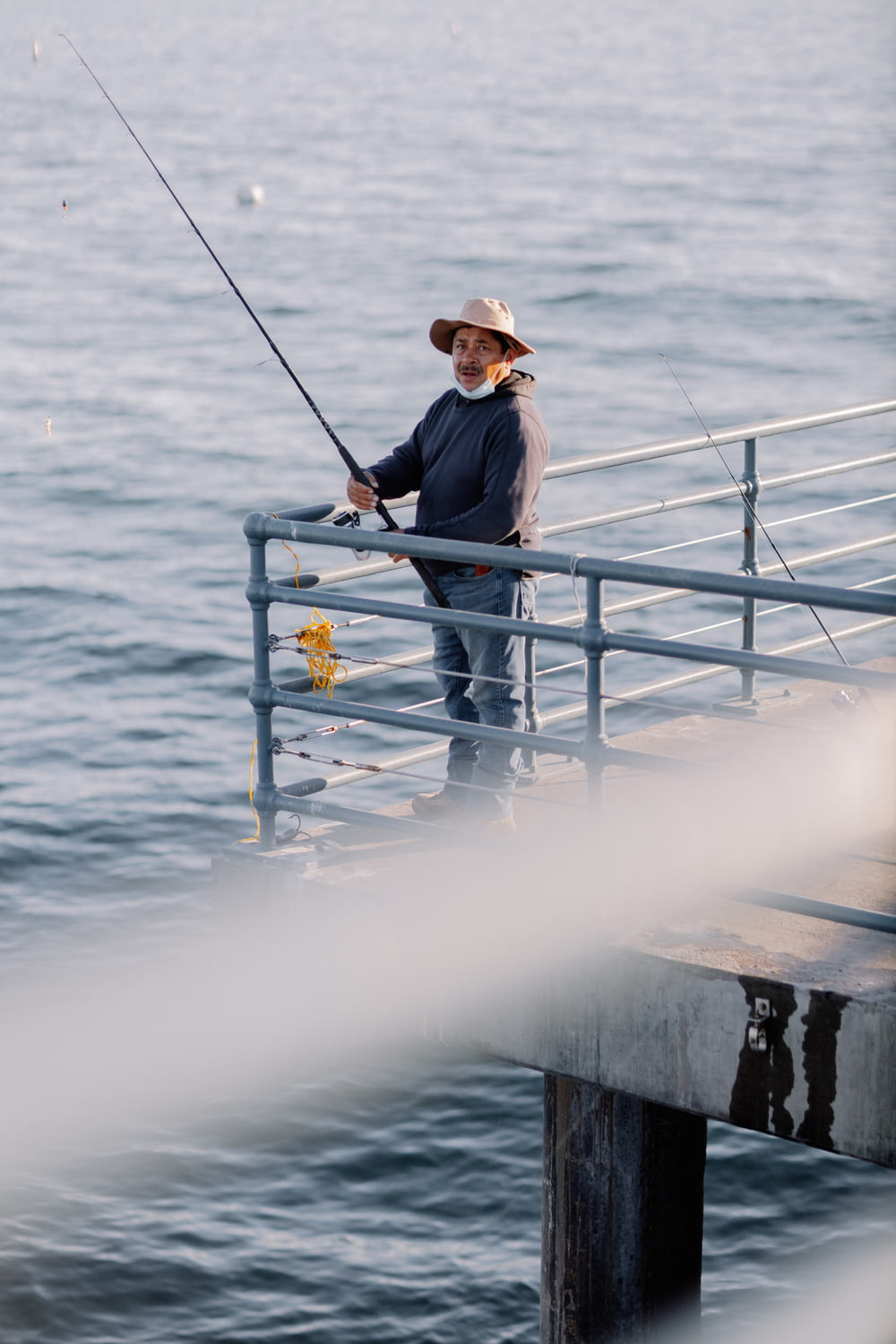 man in black jacket and brown hat sitting on white metal railings near body of water