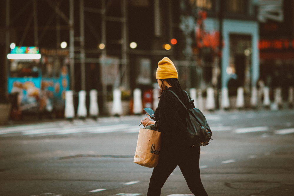 person in black jacket and yellow knit cap carrying brown plastic bucket