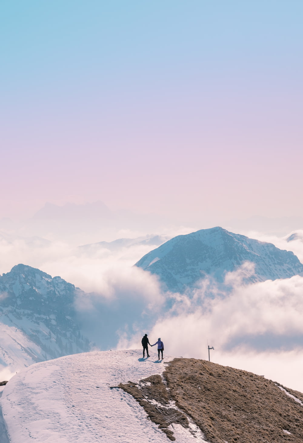 2 people walking on snow covered ground during daytime