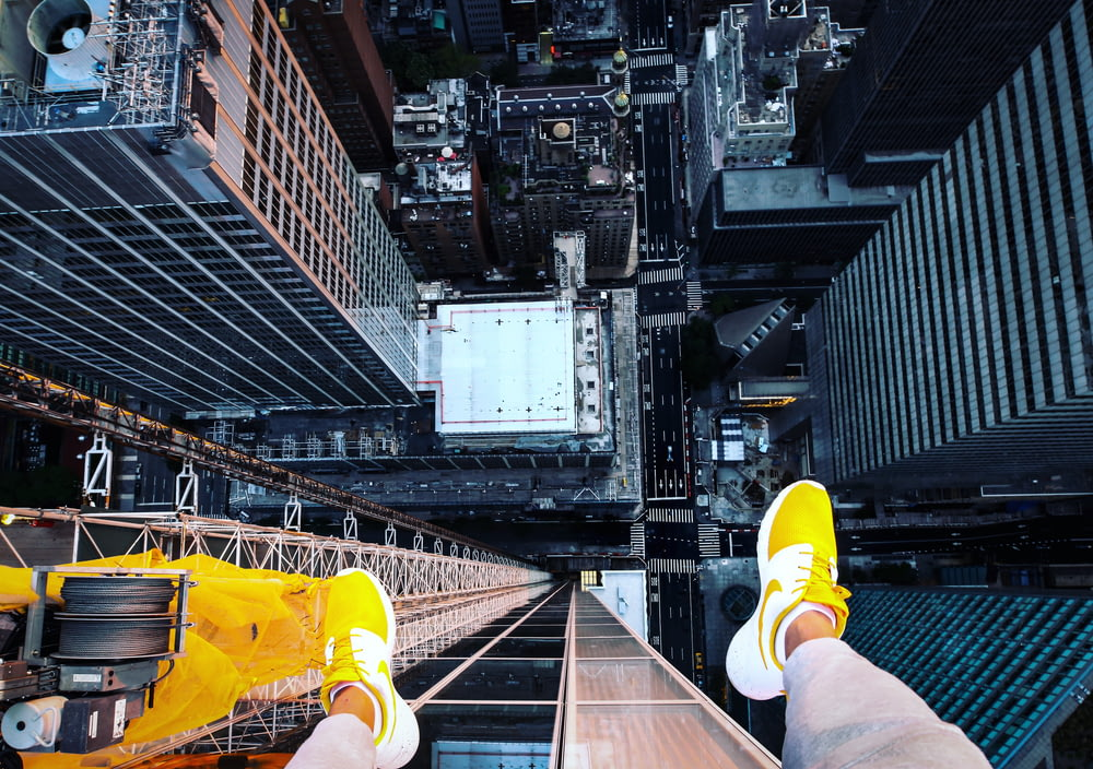 person in white pants and yellow sneakers sitting on the edge of a building